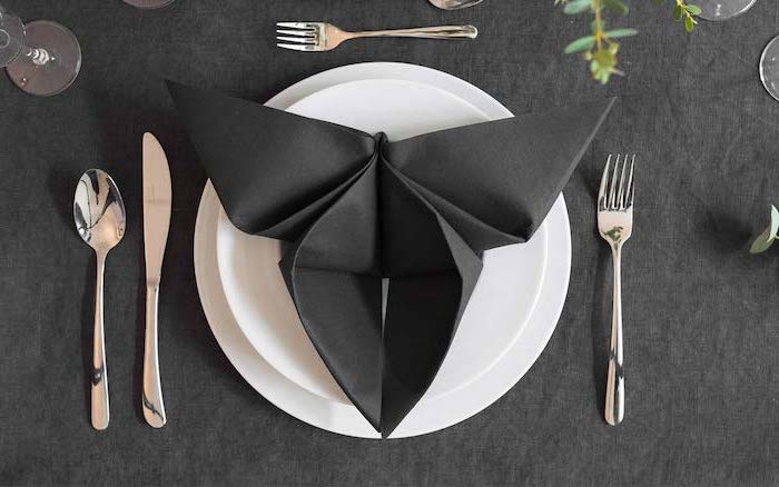 napkin folding, butterfly shaped, black napkin, on a white plate, arranged silverware around