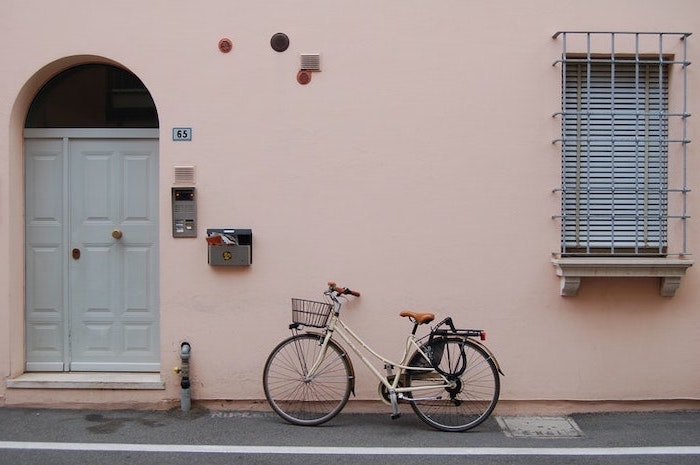 bicycle standing in front of a pink wall, pink background tumblr, white door
