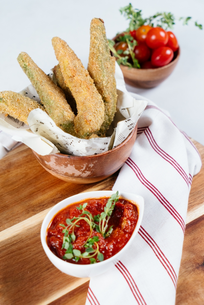 wooden cutting board, tomato sauce and cherry tomatoes in small bowls, finger food recipes, avocado fries