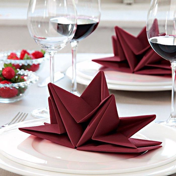 star shaped, red napkin, napkin folding, wine glasses around, white plates