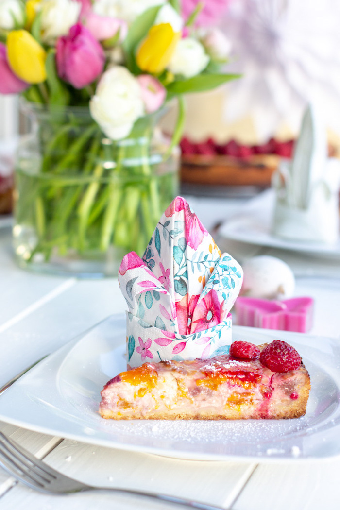 floral napkin, in a white plate, strawberry cheesecake piece, christmas napkin folding