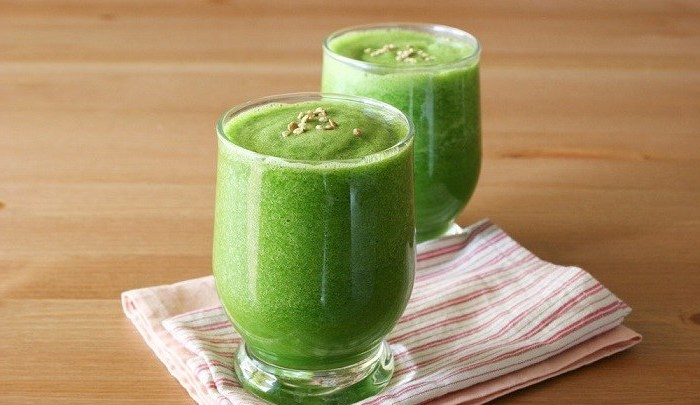 green smoothie, in two glasses, on a colourful cloth, on a wooden table, how to make a strawberry smoothie