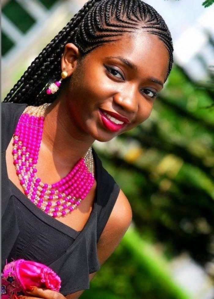girl smiling, wearing a black top, pink jewellery, with black hair, big cornrows hairstyles