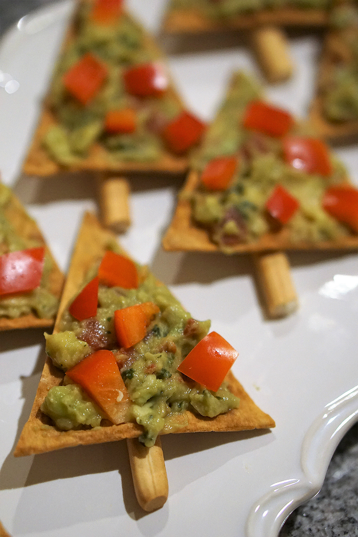 triangle shaped crackers, avocado and tomatoes on top, easy vegan appetizers, in a white plate