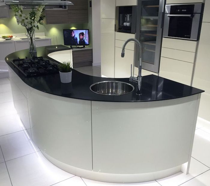 curved kitchen island, island countertop, white tiled floor, white cabinets, black countertop