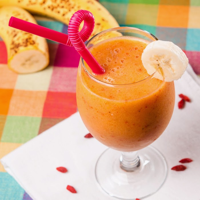 wine glass, green smoothie recipe, pink curved straw, on a white napkin, goji berry, banana slice on the rim