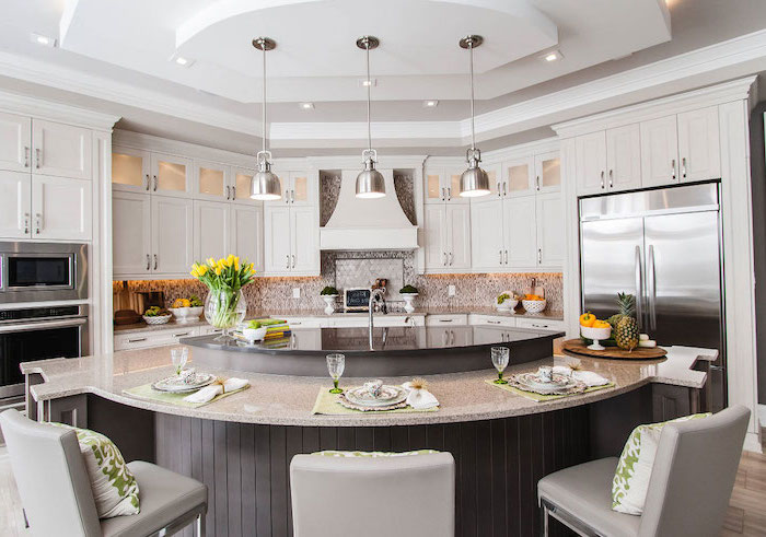 curved kitchen island, grey leather bar stools, green throw pillows, white cabinets, island countertop