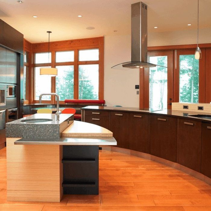 island countertop, wooden floor, curved kitchen island, wooden cabinets, black countertops