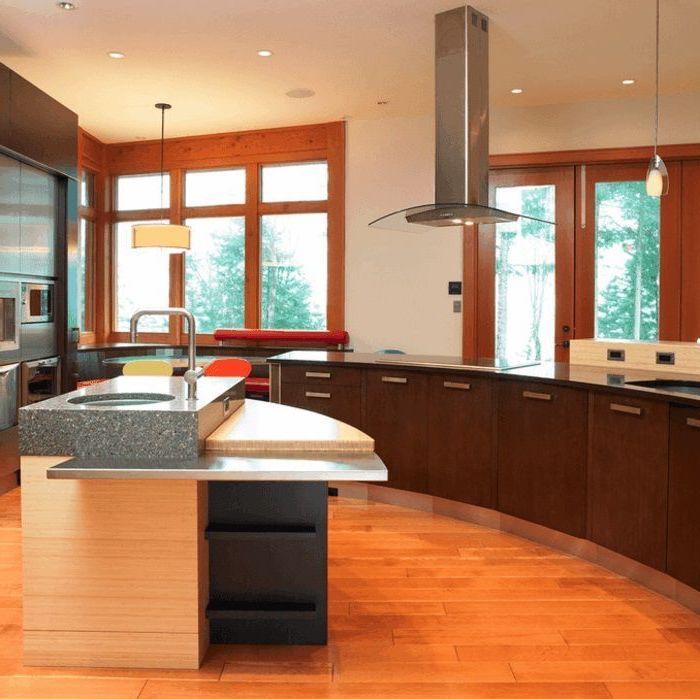 island countertop, wooden floor, curved kitchen island, wooden cabinets, black countertops