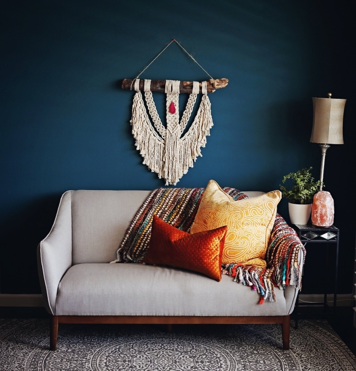blue wall, macrame tutorial, grey sofa, red adn yellow throw pillows, colourful blanket