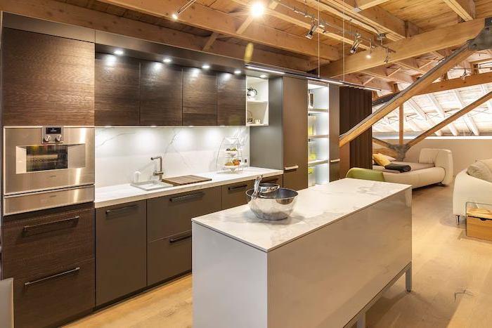 dark wooden cabinets, wooden floor, marble countertops and backsplash, kitchen island breakfast bar