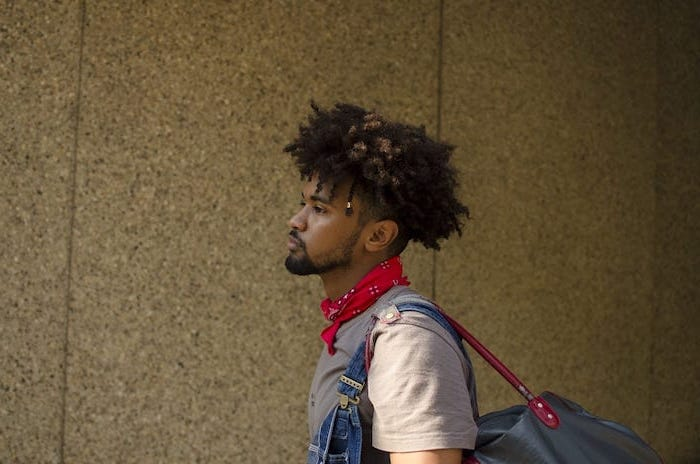 long curly hair, denim overalls, best haircuts for men, red bandana, black beard