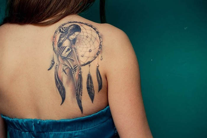 indian woman, large dreamcatcher, shoulder tattoo, upper arm tattoos, blue top, green background