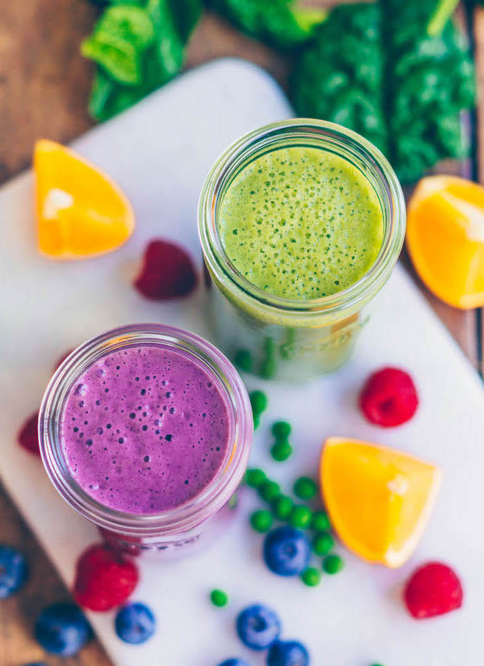 green and purple smoothie, green smoothie recipe, fruits scattered around, on a white board