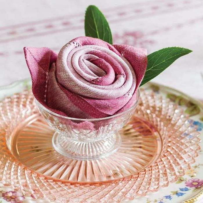 pink napkin, in the shape of a rose, inside a glass bowl, napkin folding, floral plate