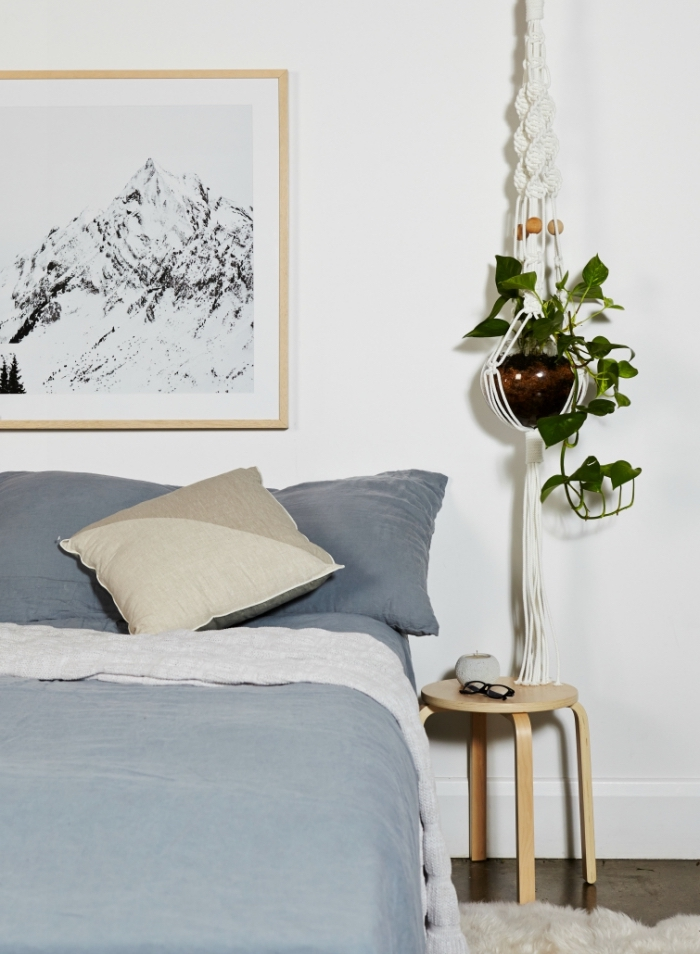 plant hanger, potted plants, blue bed linen, framed black and white photo, macrame tutorial