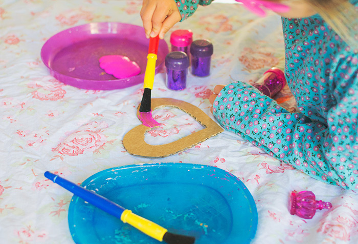 fun indoor activities for kids, blue and pink plastic plates, paint inside, girl painting a heart