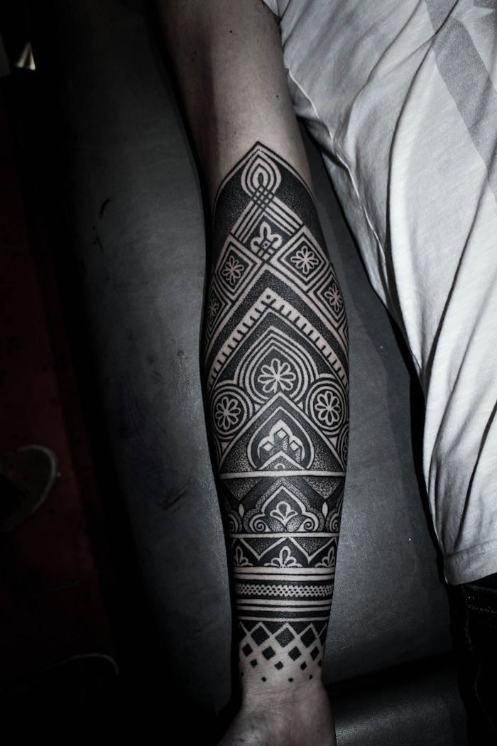 arm tattoos for girls, white top, black leather bed, geometrical forearm sleeve