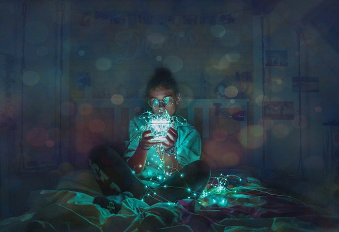 girl sitting on a bed, holding fairy lights, black and white tumblr