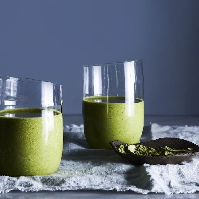 two glasses, with green smoothies inside, how to make a fruit smoothie, blue background