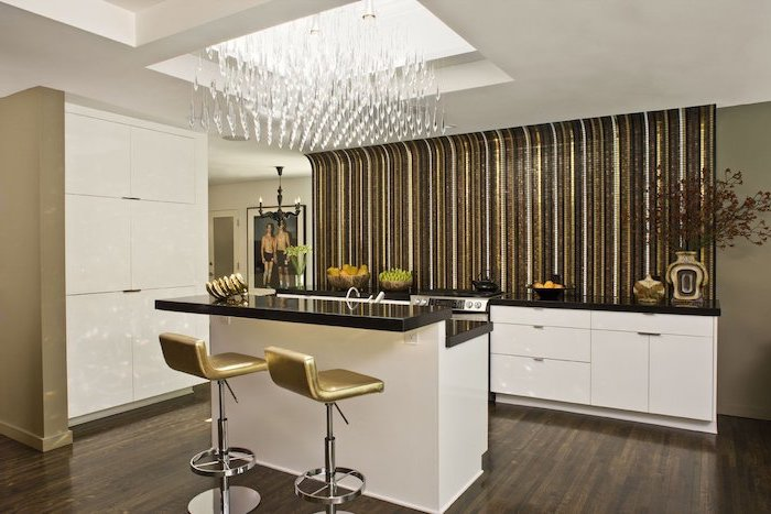dark wooden floor, gold leather bar stools, large kitchen island with seating, accent wall in gold and black
