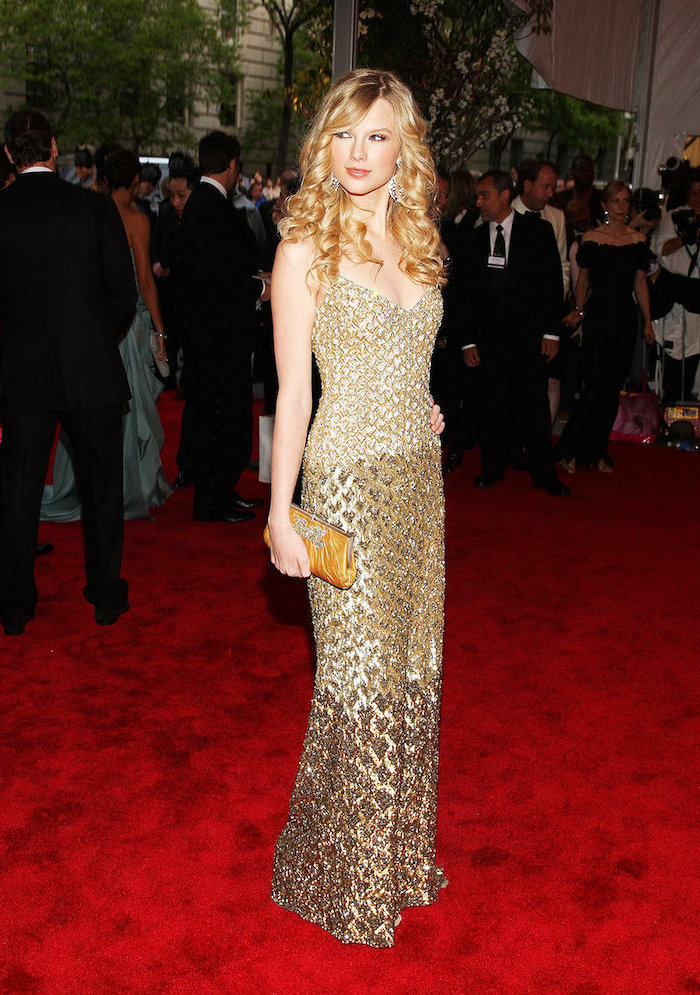 long urly blonde hair, taylor swift, met gala dresses, long gold dress, gold clutch bag