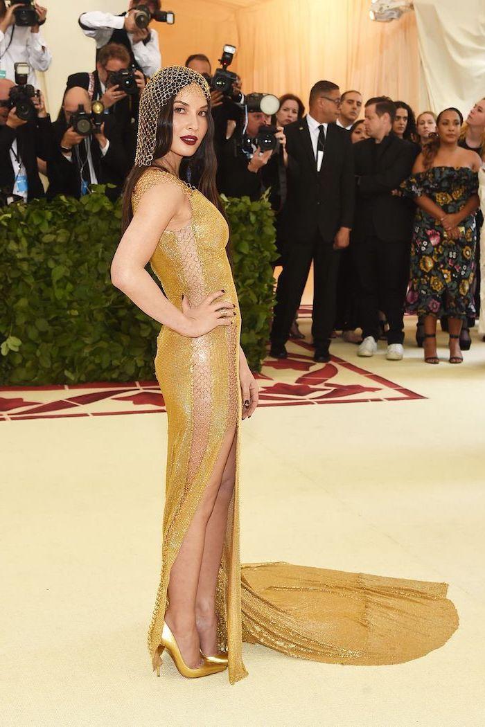 met gala 2017, olivia munn, wearing a gold sequinned dress, golden headpiece, gold metallic heels