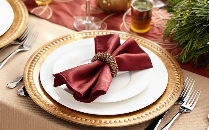 how to fold napkins, red bow shaped napkin, gold ring around it, on white and gold plates