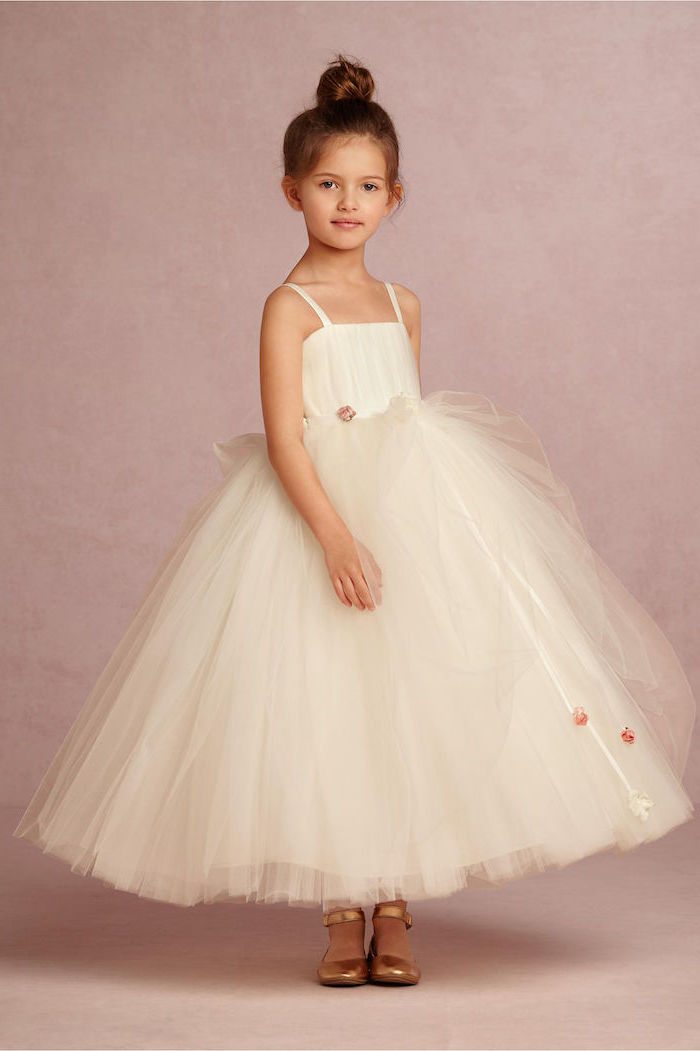 flower girl hair, white tulle dress, brown hair, messy bun, gold shoes, pink background