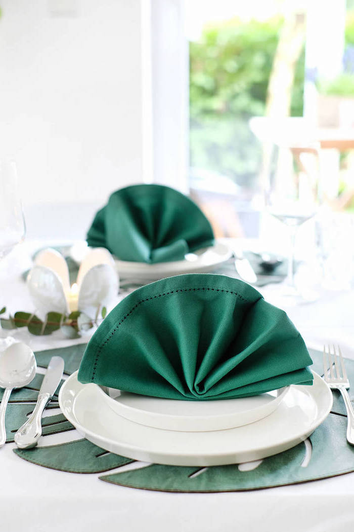 green napkins, in the shape of a fan, on white plates, paper napkin folding, silverware around it