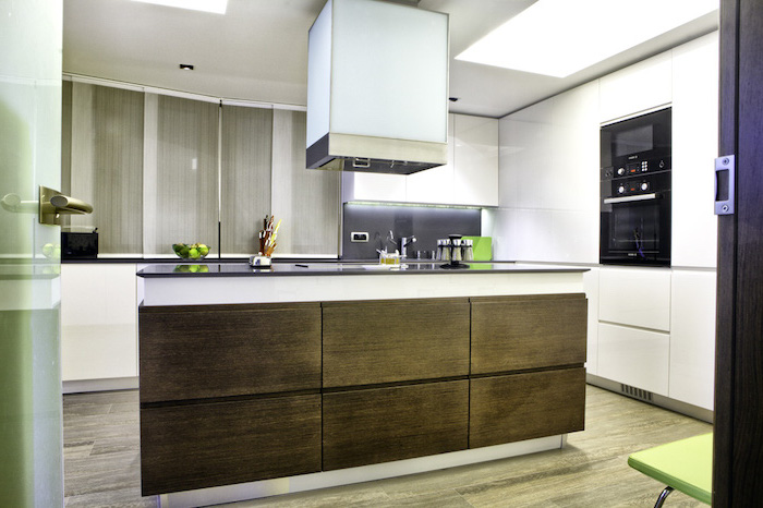 wooden drawers, white walls, white cabinets, large kitchen island with seating, wooden floor