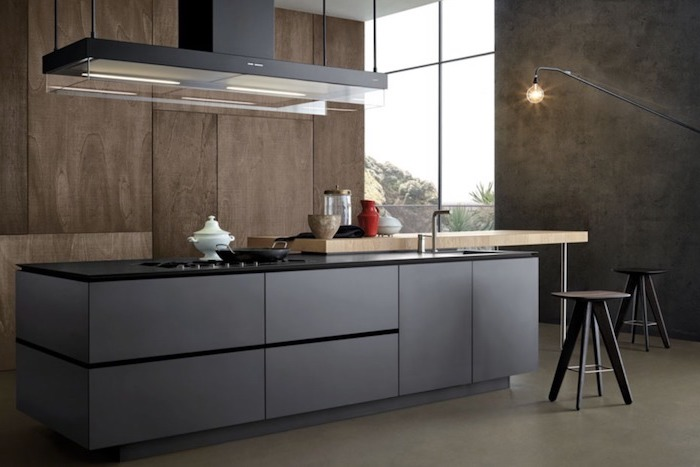 wooden wall, grey cabinets and drawers, metal bar stools, large kitchen island with seating