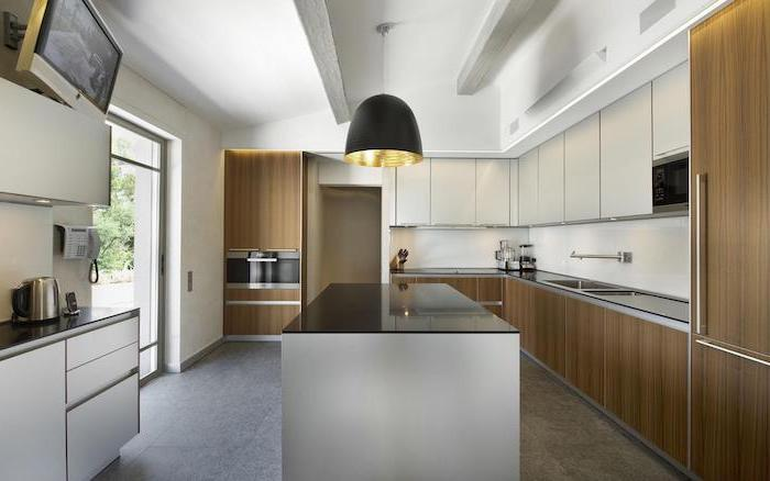 granite tiled floor, wooden cabinets and drawers, black countertops, narrow kitchen island