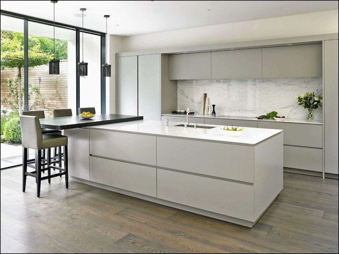 marble backsplash, kitchen island ideas, white kitchen island, wooden floor, grey leather bar stools
