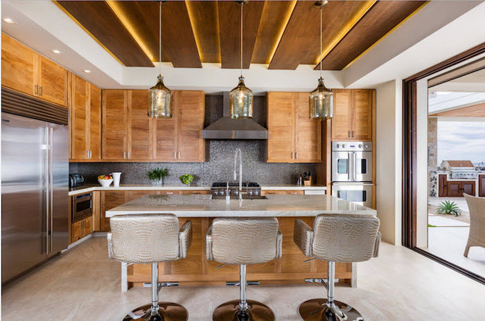 silver leather bar stools, narrow kitchen island, wooden cabinets and drawers, marble countertops