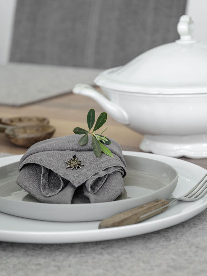 cloth napkin folding, grey napkin, in a grey plate, wooden fork handle
