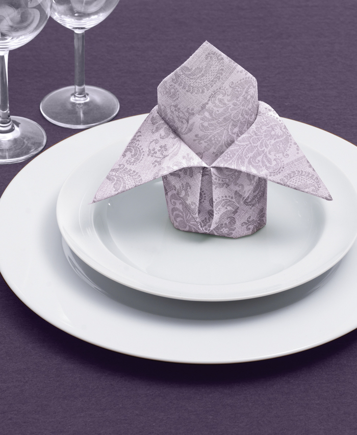 grey patterned napkin, on white plates, purple table cloth, cloth napkin folding