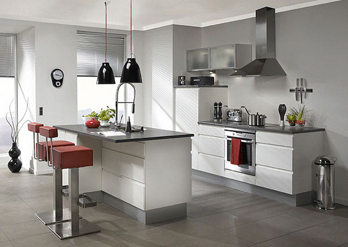 red leather bar stools, narrow kitchen island, white cabinets and drawers, black countertops, tiled floor