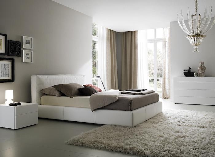 white leather bed, grey tiled floor, white carpet, master bedroom decor, framed art, tall windows
