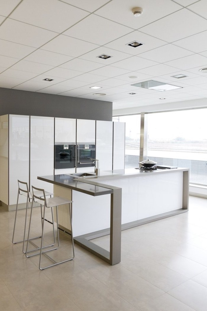 white tiled floor, metal bar stools, white cabinets, island cabinets, grey countertops, large windows