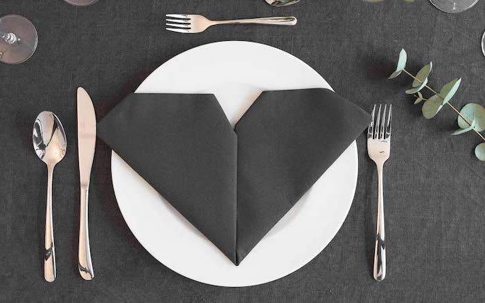 heart shaped, black napkin, on a white plate, fancy napkin folding, black table cloth