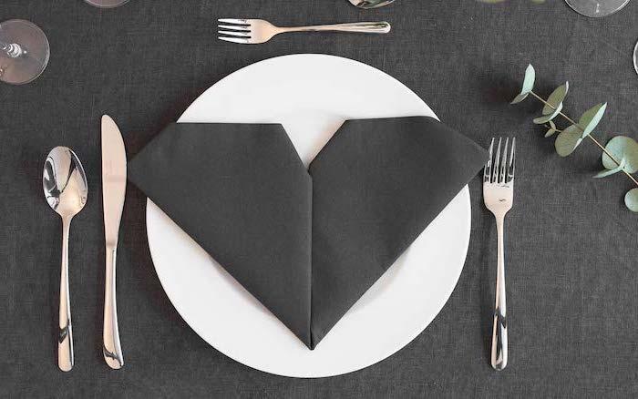heart shaped, black napkin, on a white plate, fancy napkin folding, black table cloth