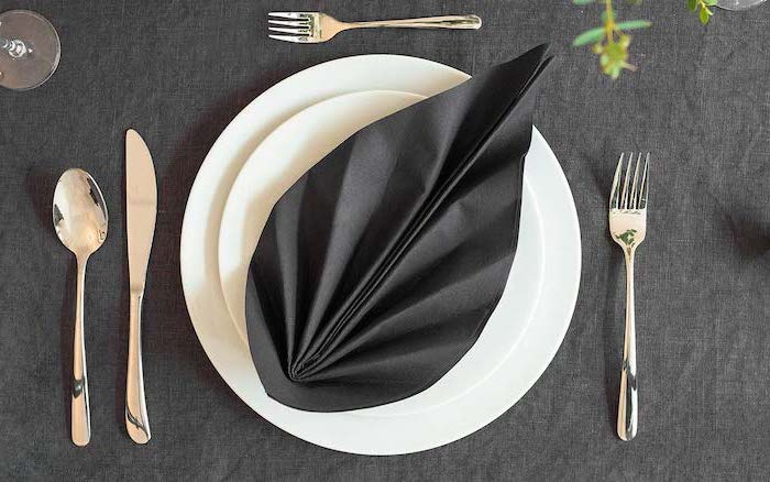 black napkin, in the shape of a leaf, how to fold napkins, silverware arranged, around white plates