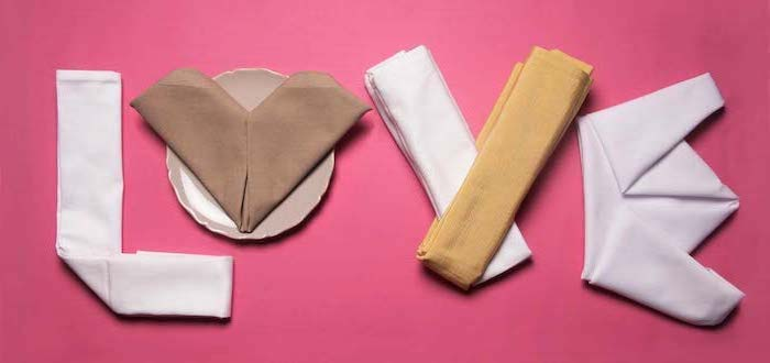 pink background, fancy napkin folding, love written with napkins