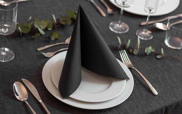 black folded napkin, on white plates, silverware arranged around them, napkin folding with rings