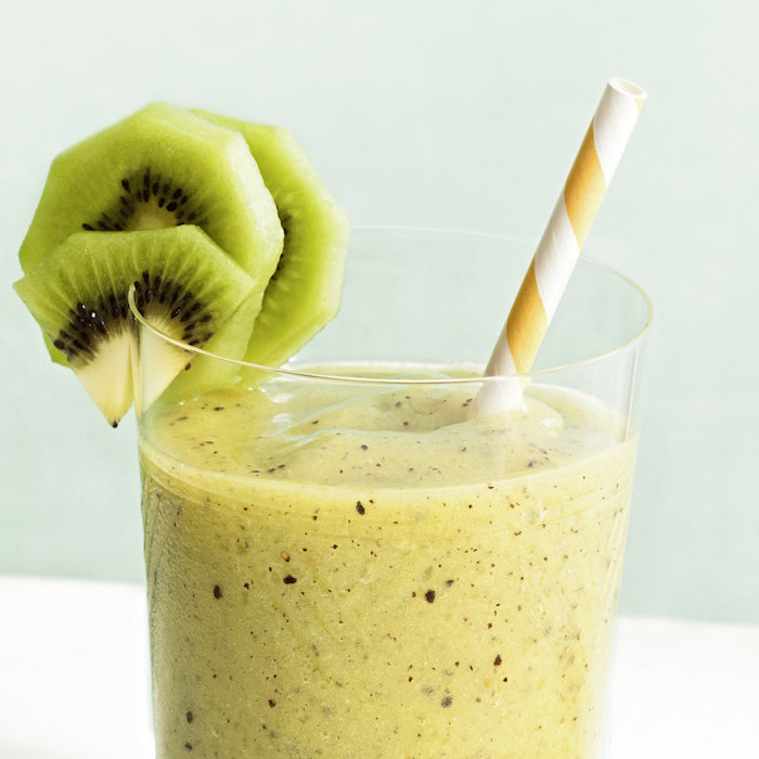 how to make a banana smoothie, orange and white paper straw, kiwi slices on the rim