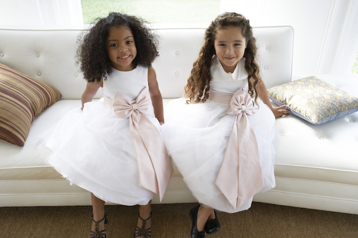 two girls sitting on a white sofa, wearing white dresses, with ivory bows, flower girl hair, curly hair