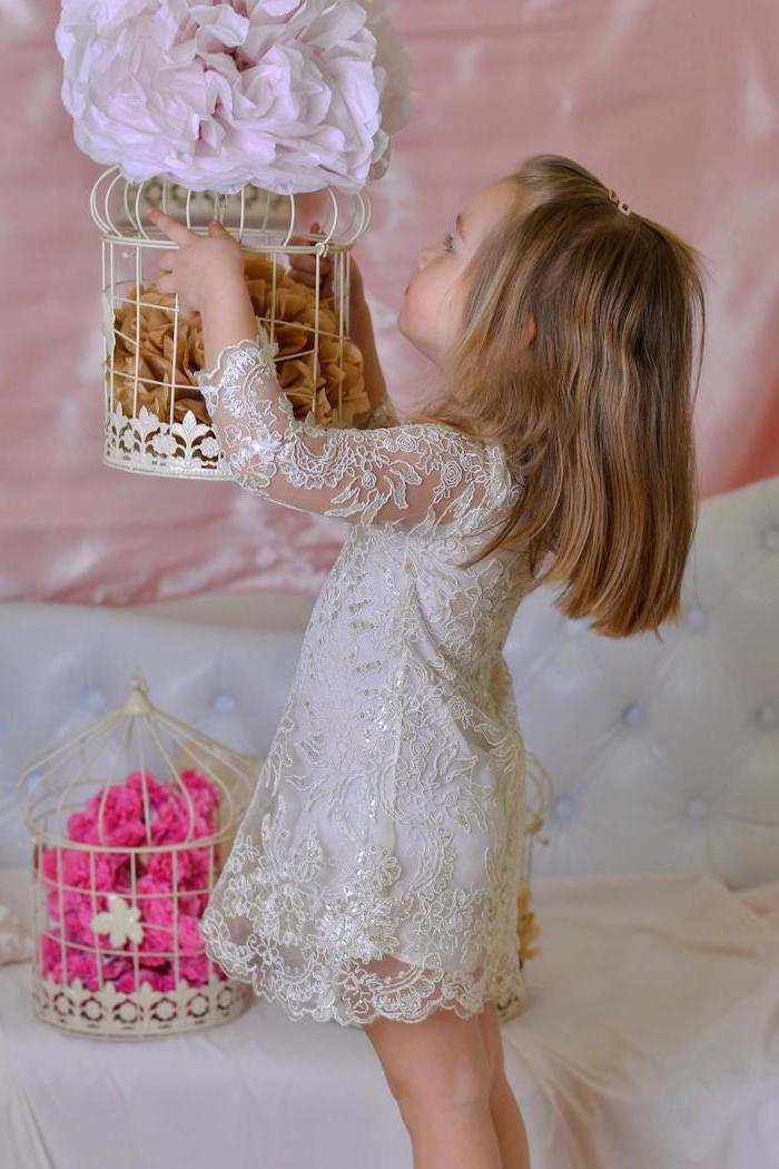 flower in bird cages, little girl holding them, dressed in white lace dress, flower girl dress, short brown hair