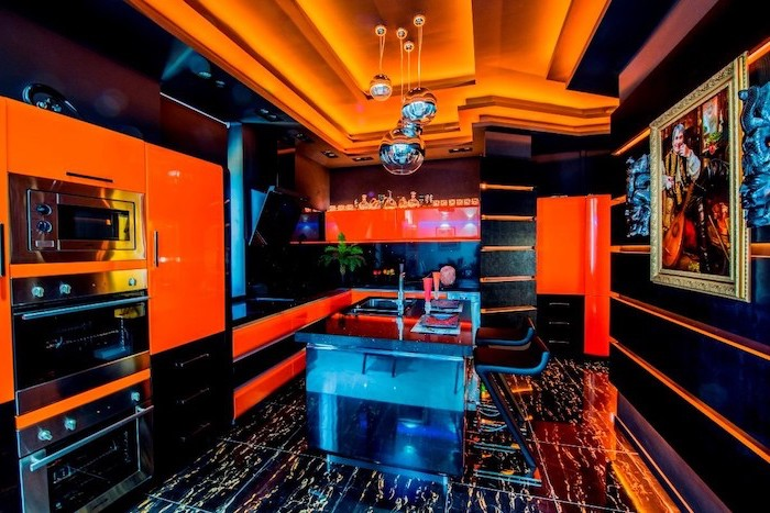 black and orange kitchen, led lights, black leather bar stools, kitchen island with stove, black tiled floor