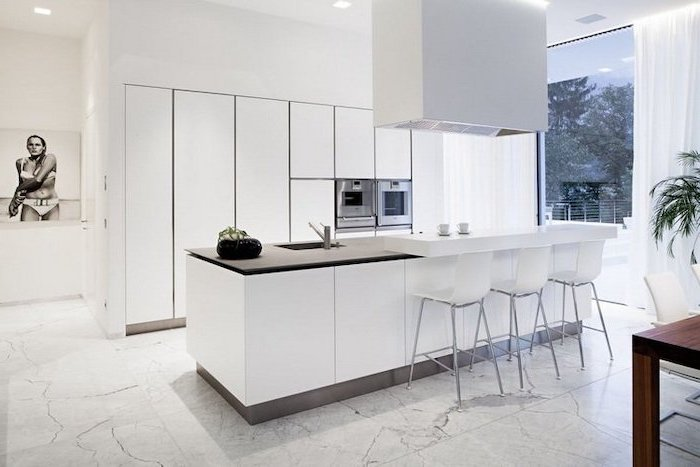 white cabinets, kitchen island with stove, white bar stools, marble tiled floor, black countertop
